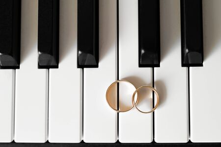 Wedding gold rings lie on the piano keys. Stok Fotoğraf - 133141808