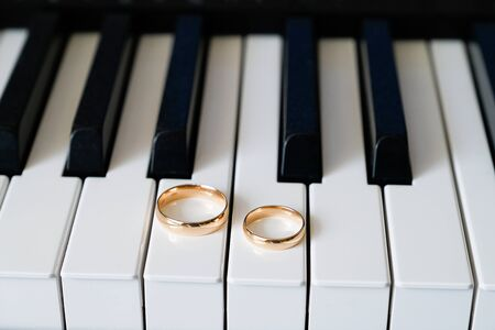 Wedding gold rings lie on the piano keys. Stok Fotoğraf