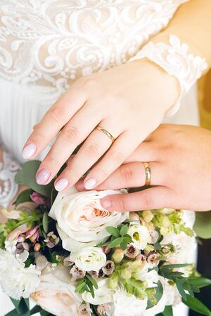 Hands of the bride and groom on the wedding bouquet. Stock Photo