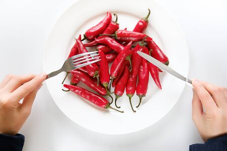 Girl hands with fork and knife, woman cuts red hot spicy Cayenne pepper on a white plate. Proper nutrition, vegetarian food, healthy lifestyle diet concept. Stok Fotoğraf - 132719745