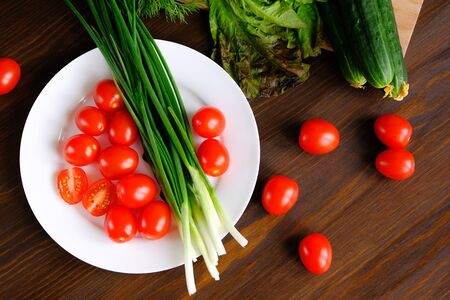 Tomatoes and green onions on a plate. Near cucumbers, green salad. Vegetables from the garden. Natural organic farm agricultural products, vegetarianism. Marinating for the winter, harvest. Home life. Stok Fotoğraf - 133067506