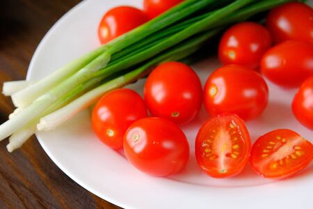 Tomatoes and green onions on a plate. Vegetables from the garden. Natural organic farm agricultural products, vegetarianism, veganism, raw food. Canning for the winter, harvest. Home life. Stok Fotoğraf - 133066920