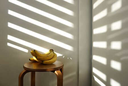 Bananas lie on a wooden chair in natural light. The concept of vegetarianism, veganism, raw food, healthy eating and diet. Stok Fotoğraf - 133076959
