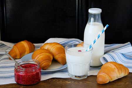 Croissants on a plate, raspberry jam, milk in a bottle and in a glass with a straw on a linen towel on a wooden table. The concept of healthy eating. Organic farm products for Breakfast or lunch. Stok Fotoğraf - 133141818