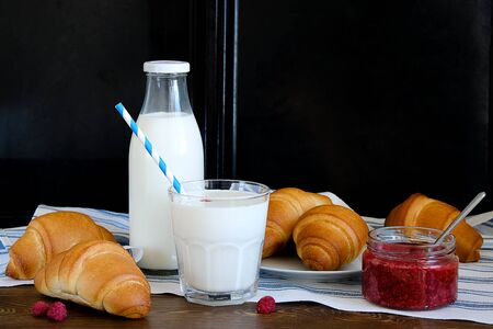 Croissants on a plate, raspberry jam, milk in a bottle and in a glass with a straw on a linen towel on a wooden table. The concept of healthy eating. Organic farm products for Breakfast or lunch. Stok Fotoğraf - 133141819
