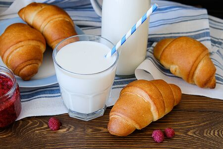 Croissants on a plate, raspberry jam, milk in a bottle and in a glass with a straw on a linen towel on a wooden table. The concept of healthy eating. Organic farm products for Breakfast or lunch. Stok Fotoğraf - 133141821
