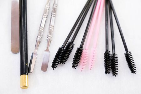 A set of brushes and pencil makeup artist for professional makeup in front of a mirror in a beauty salon, the concept of cosmetology, modeling and correction of the eyebrow line, self-care. Stok Fotoğraf - 133077912