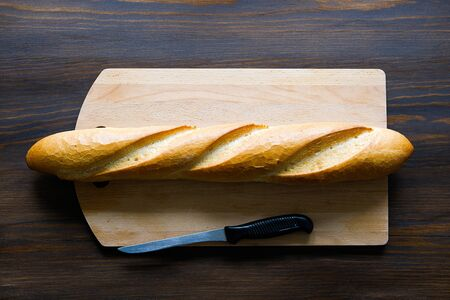 Freshly baked bread, kitchen knife with black plastic handle, cutting Board on a wooden table, close-up. Copy space for text. The concept of kitchen utensils, cooking. Stok Fotoğraf - 133077106