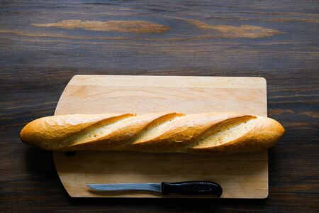 Freshly baked bread, kitchen knife with black plastic handle, cutting Board on a wooden table, close-up. Copy space for text. The concept of kitchen utensils, cooking.