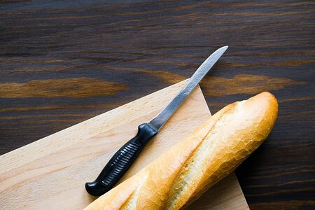 Freshly baked bread, kitchen knife with black plastic handle, cutting Board on a wooden table, close-up. Copy space for text. The concept of kitchen utensils, cooking. Stok Fotoğraf - 133141832