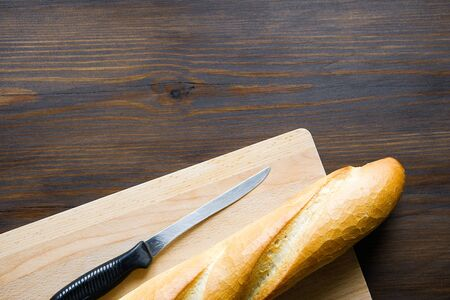 Freshly baked bread, kitchen knife with black plastic handle, cutting Board on a wooden table, close-up. Copy space for text. The concept of kitchen utensils, cooking. Stok Fotoğraf - 133141833