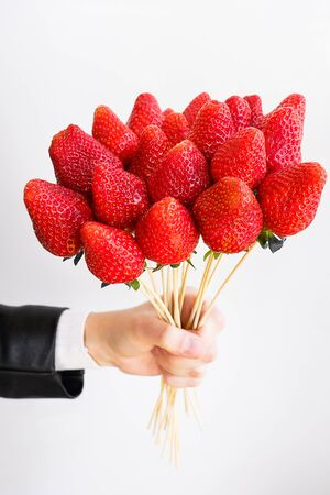Alternative edible bouquet of berries in the hand of a man or woman, birthday, Valentine's Day, holiday, close-up. Whole strawberry fruit on wooden skewers, on a white background. Selective focus. Stok Fotoğraf - 133077268