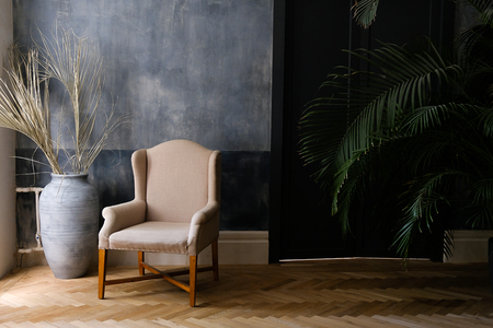 Beige chair and a large vase near the window in the hall, next to a palm tree near the door. Stok Fotoğraf - 133171879