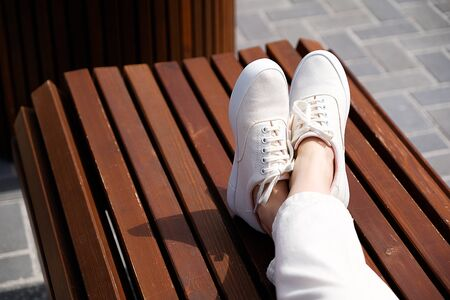 Feet girl in white shoes on a bench in the Park. Close up.