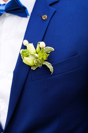 A young man or groom in a white shirt, bow tie and blue vest or jacket. Beautiful boutonniere of white roses and green leaves in a vest pocket or lapel. Wedding theme. Stok Fotoğraf - 134741010