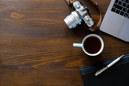 A laptop, a Cup of tea, a camera and a notebook lie on a dark wooden table. The workplace of a photographer or a freelancer. Copy paste for text. Stok Fotoğraf - 134741034