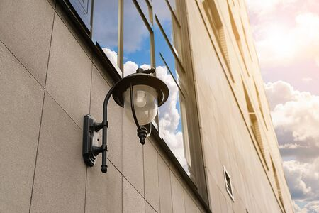 Street lighting on the facade of the building against the blue sky. Stok Fotoğraf