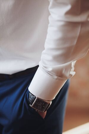Man's hand in the pocket of stylish trousers close-up. A successful young man who is a businessman, entrepreneur, expensive watches, fashionable in a simple white shirt. Blurred background. Stok Fotoğraf - 134740723