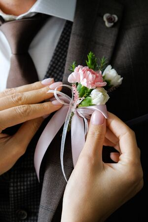 The brides hands adjust the boutonniere on the grooms wedding jacket