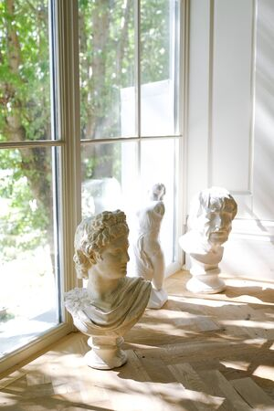 Old sculptures on the windowsill. In the background is a glass window.