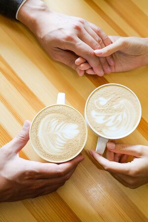 A couple holding hands in a cafe, drinking coffee, the hands of lovers on the background of a wooden table. Breakfast or lunch in the restaurant. Engagement, guy firmly holds his girlfriend's hand. Stok Fotoğraf - 134740784