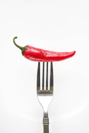 Red hot chili pepper on a fork.