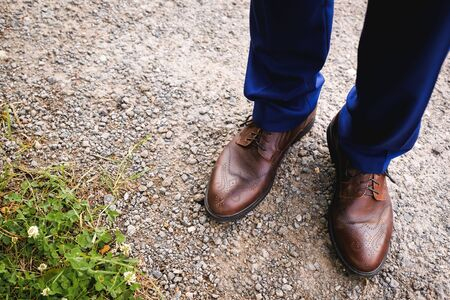 The feet of the groom, businessman or entrepreneur in expensive luxury leather brown shoes with a pattern on the background of grass and cobblestones. Zdjęcie Seryjne