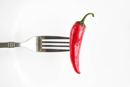 Red hot chili pepper on a fork. The concept of healthy eating. Stockfoto