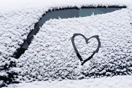 The heart is painted on the glass of the car, on the background of snow. Symbol of love, romance, Valentines Day.