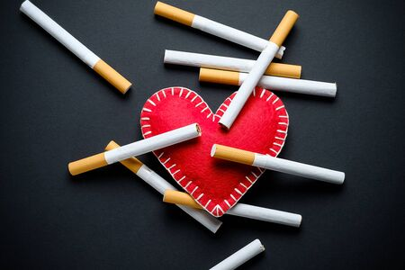 Red Decorative Heart And Cigarettes, On A Black Background. Smoking Destroys Health. social problem.