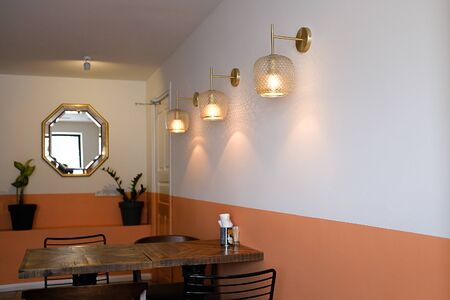 Interior Of A Cafe Or Fast Food Restaurant. An Old Wooden Table And Chairs Against A White And Orange Wall. Stok Fotoğraf