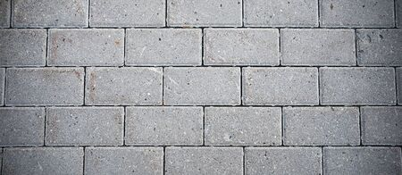 Gray Brick Wall Of A New Building Or Sidewalk. Textured Background Or Banner.