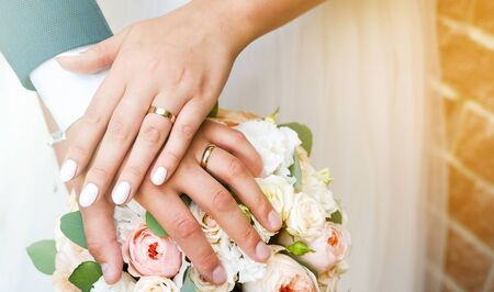 Hands Of The Bride And Groom On The Wedding Bouquet. Stok Fotoğraf