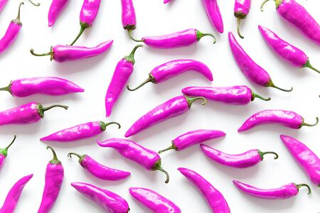 Hot Chili Pepper On A White Background, Non-Standard Purple Color. The concept of GMO Products. Stack Of Vegetables.