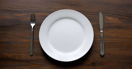 Cutlery And An Empty Clean White Plate, On A Wooden Background. Fork And Spoon Near The Bowl. The Concept Of Food. Copy The Space For The Text. Banner.