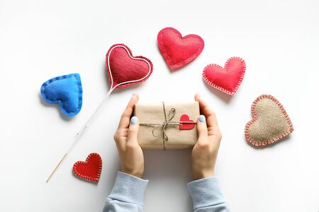 Womens Hands Hold A Gift In Wrapping Paper, For Valentines Day. Red And Blue Decorative Valentines And Hearts. The concept of handmade.