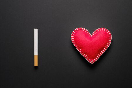 Red Decorative Heart And Cigarette, On A Black Background. Smoking Destroys Health. social problem.