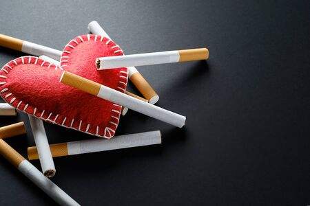 Cigarettes Lie On A Red Decorative Heart, On A Black Background. Smoking Destroys Health. social problem. Stok Fotoğraf