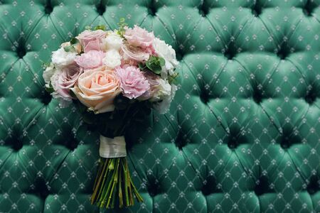 Beautiful Wedding Bouquet On A Luxurious Velour Background, Close-Up. A Bouquet Of Different Flowers And Green Leaves Tied With A Satin Ribbon, Blurred Background. wedding theme.
