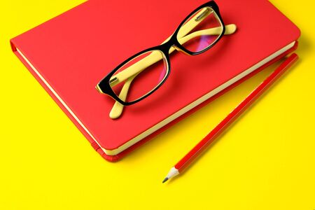 The glasses are On a Red Notebook, next to a pencil, On a Bright Yellow Background. Workplace Freelancer, Businessman, Entrepreneur.
