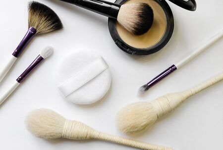 Branded Cosmetics. Mineral compact powder, sponge and various brushes for application, isolated on a white background. Selective Focus.