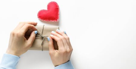 Womens Hands Tie A Gift In Wrapping Paper, On Valentines Day. Next To It Is A Red Decorative Heart Or A Handmade Valentine. Banner. Stok Fotoğraf