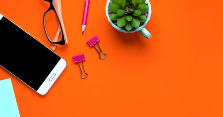 Glasses, Mobile Phone, Flower, stickers, paper Clips, Stationery On a background of lush lava. Workplace Freelancer, Businessman, Entrepreneur. Banner.