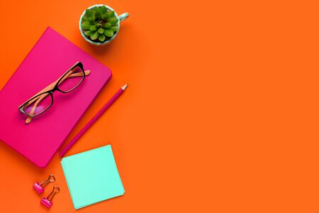 The glasses are lying on a pink notebook, next to a pencil, against a background of lush lava. Next To A Pencil, Stickers, Paper Clips And A Flower. Workplace Freelancer, Businessman, Entrepreneur.