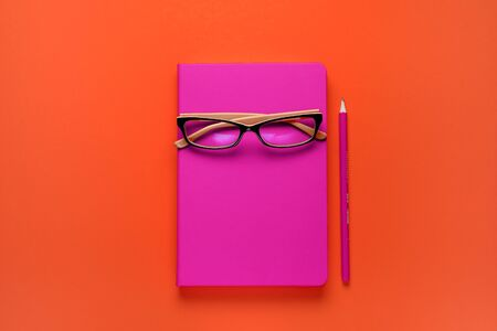 The glasses are lying on a pink notebook, next to a pencil, against a background of lush lava. Workplace Freelancer, Businessman, Entrepreneur. Stok Fotoğraf