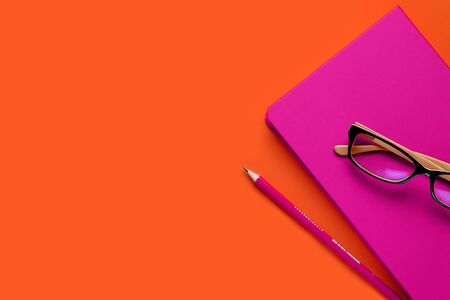 The glasses are lying on a pink notebook, next to a pencil, against a background of lush lava. Workplace Freelancer, Businessman, Entrepreneur. Copy Space For Text. Stok Fotoğraf