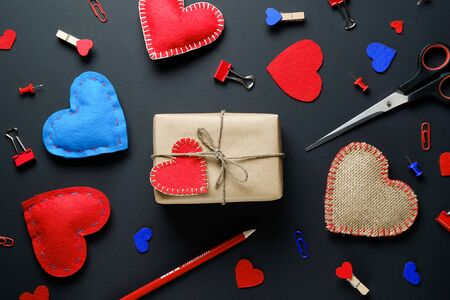 The background of Valentines day. Red And Blue Paper Clips, Clothespins, Gifts, Valentines, Ribbons, Pencils. The concept of handmade. Flat Layout.