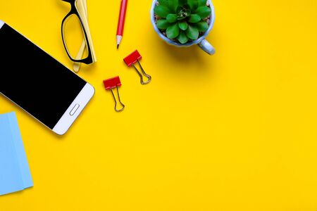 Glasses, mobile phone, flower, stickers, paper clips, stationery on a yellow background. Workplace Freelancer, Businessman, Entrepreneur. Stok Fotoğraf