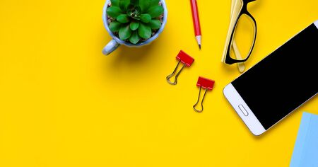 Glasses, mobile phone, flower, stickers, paper clips, stationery on a yellow background. Workplace Freelancer, Businessman, Entrepreneur. Banner Stok Fotoğraf