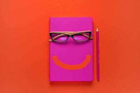 The glasses are lying on a pink notebook, next to a pencil, against a background of lush lava. A painted Smile on a Notepad. Workplace Freelancer, Businessman, Entrepreneur.